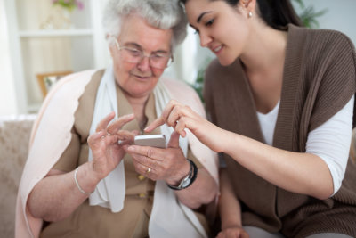 Old woman learning to use smartphone with a help of young woman